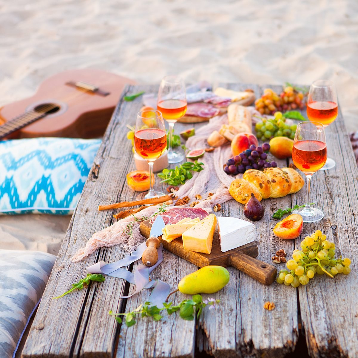 Picnic on the beach at sunset in the style of boho, food and drink
