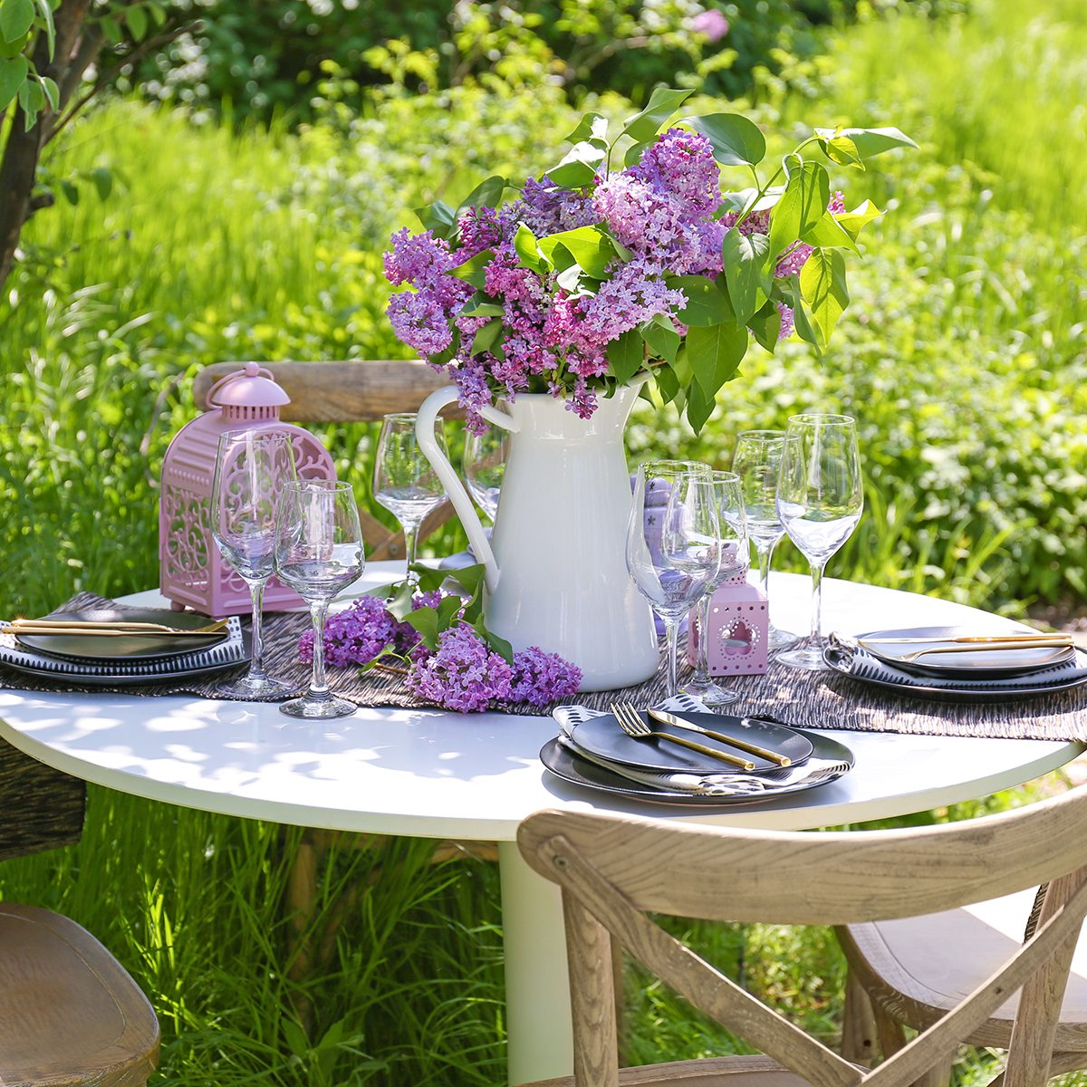 Beautiful table setting with lilac flowers decoration outdoors