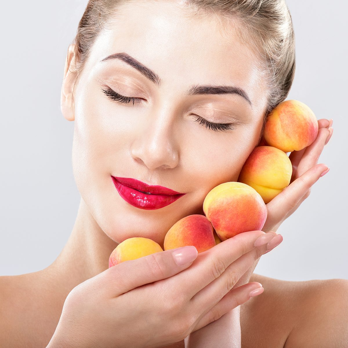 Beautiful woman holding a juicy apricots, peaches.