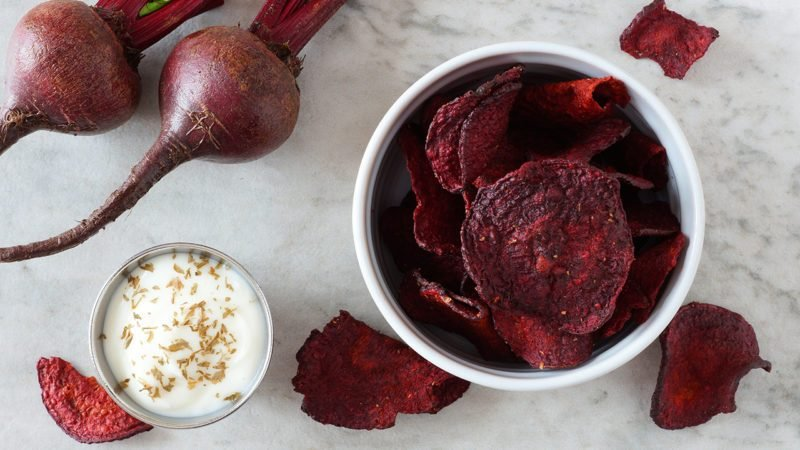 Bowl of healthy beet chips above view over a white marble background