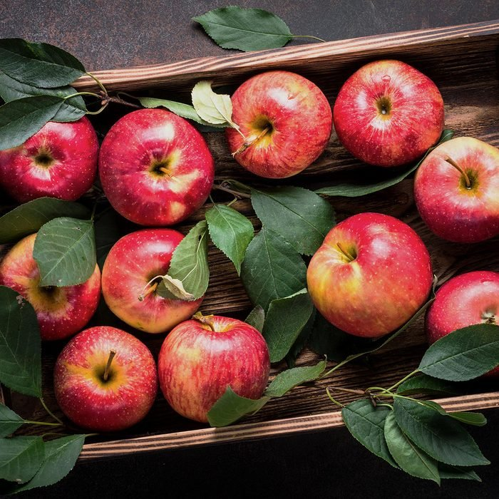 Red apples in wooden tray on dark stone table.