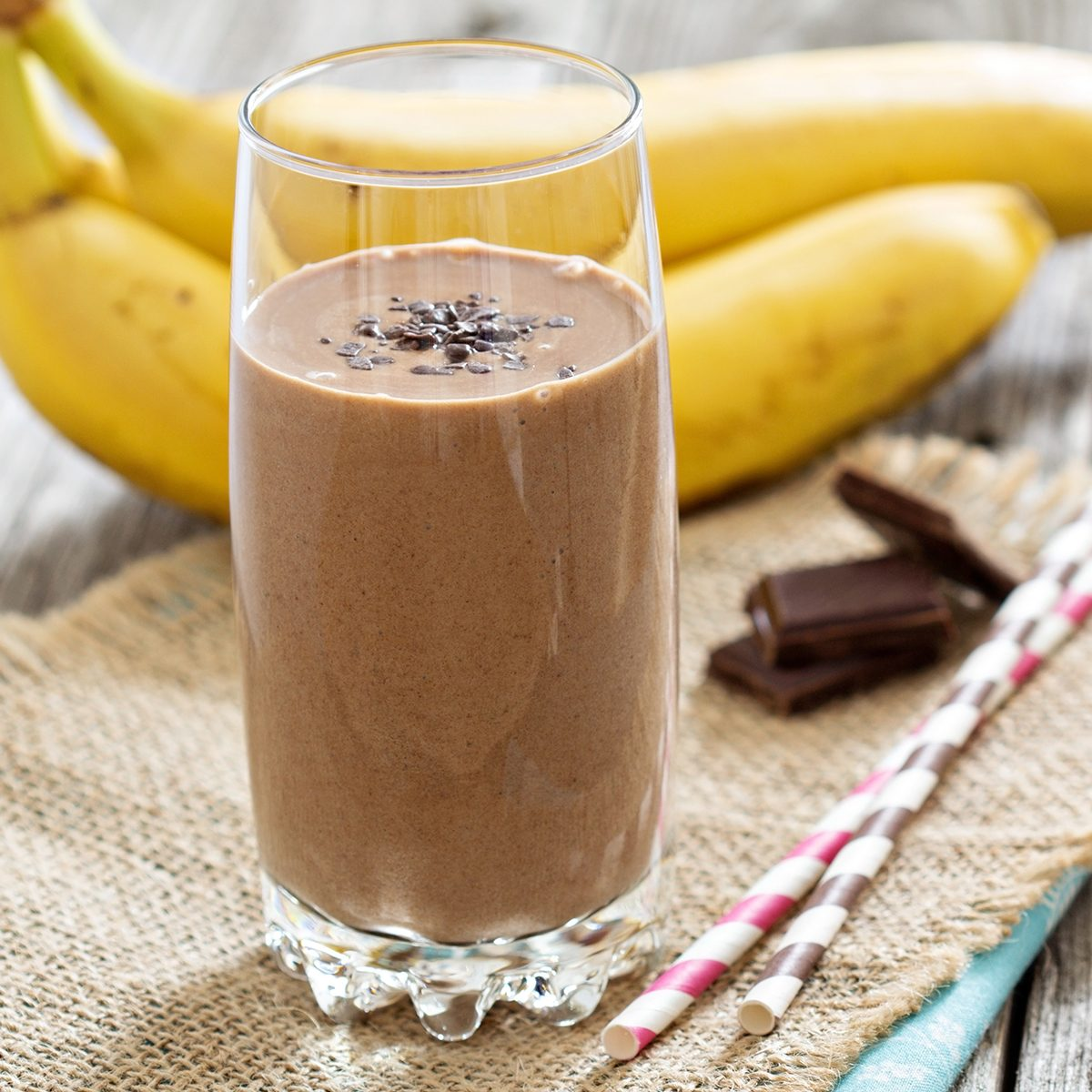Chocolate banana smoothie in a glass with straws