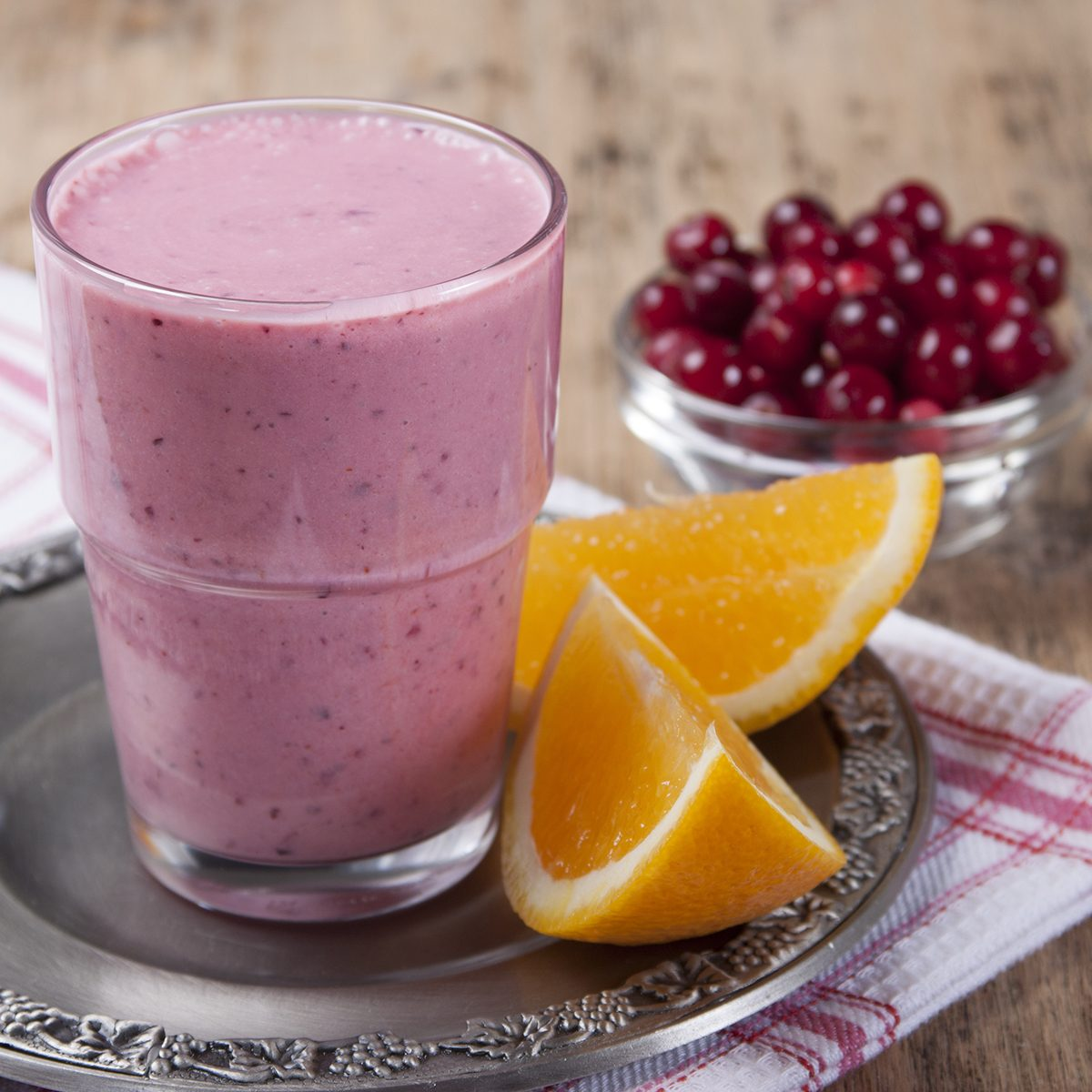 Smoothies and orange and cranberries in a glass on a wooden table.