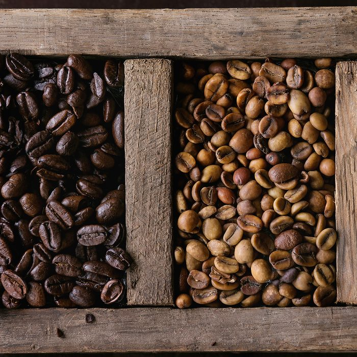 Food background with green and brown decaf unroasted and black roasted coffee beans in old wooden box