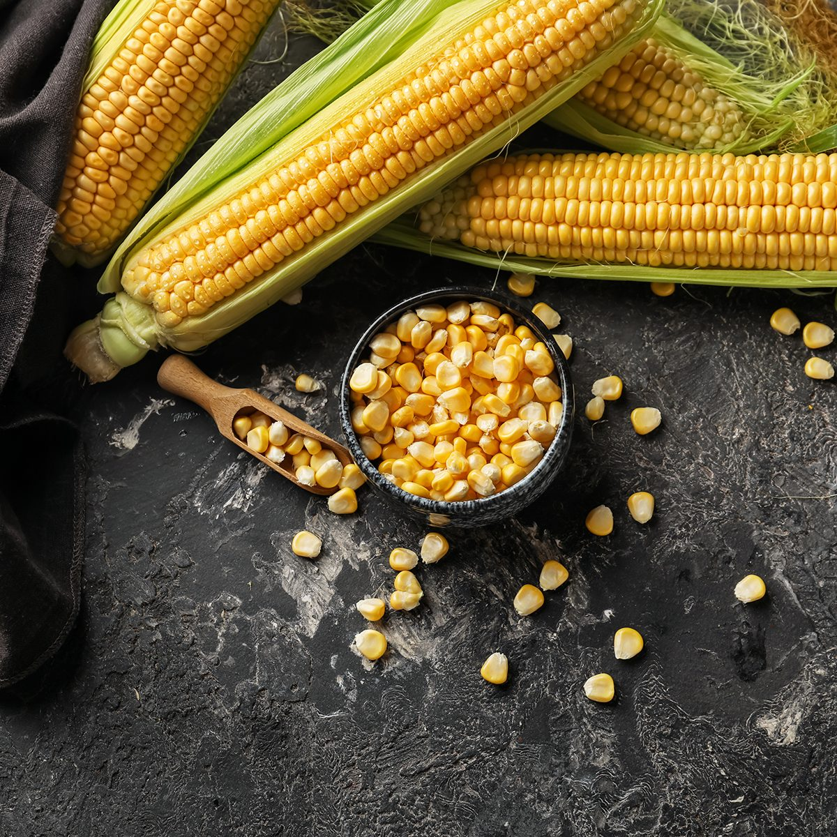 Composition with fresh corn cobs on dark background