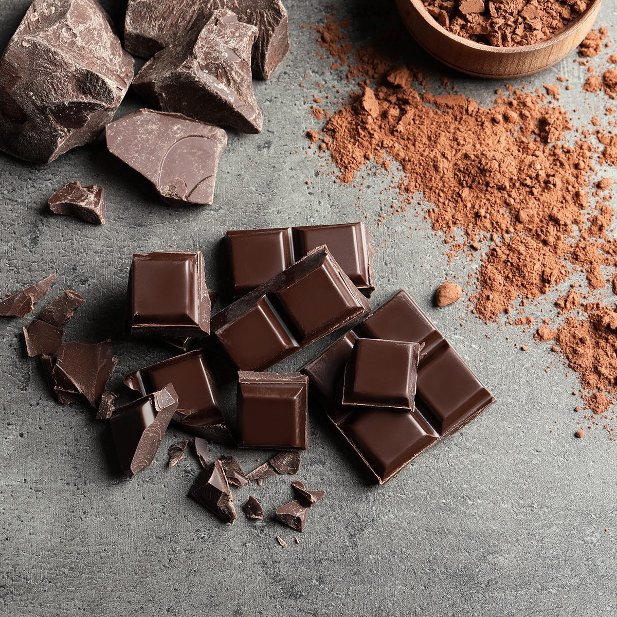 Pieces of chocolate and cocoa powder on grey background