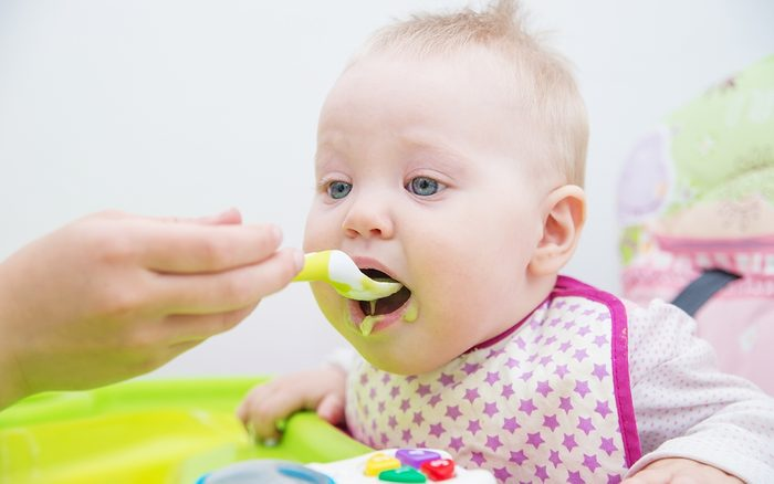 The baby learns to eat from a spoon. The first lure of the baby.