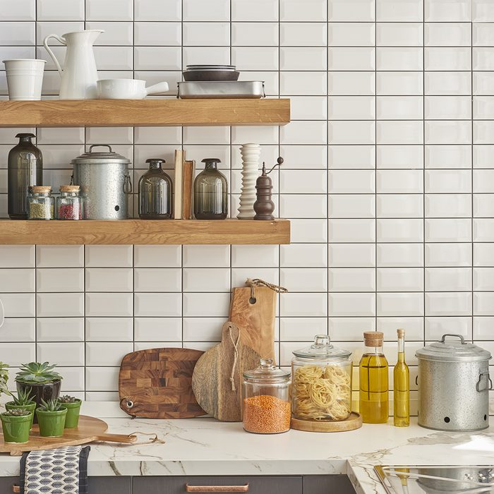 white tiles wall modern kitchen with chopping board;