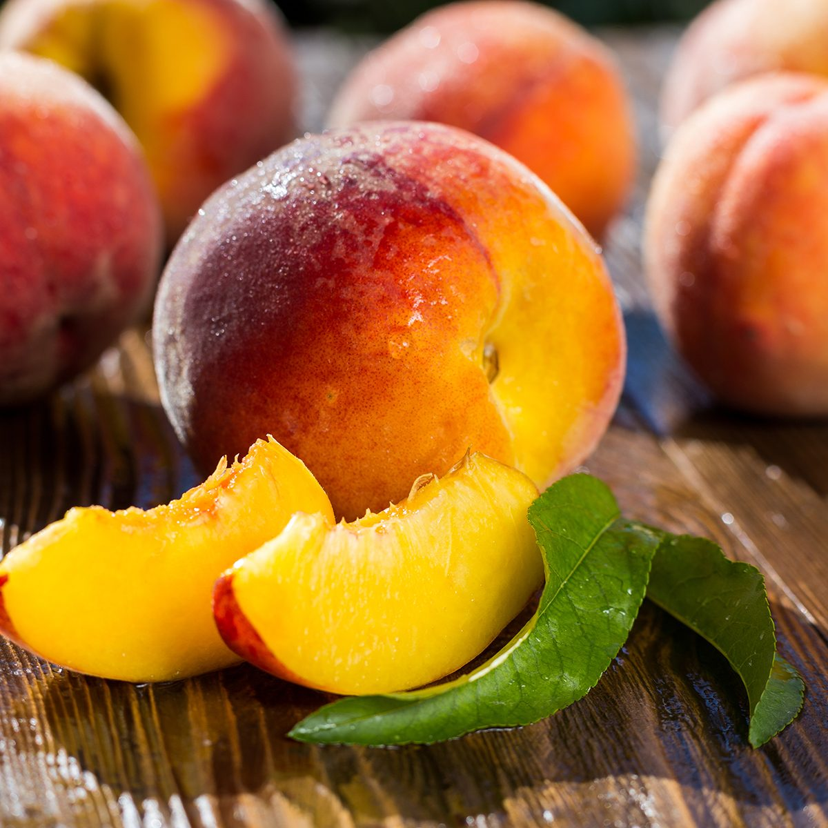 Fresh sweet group of sliced peaches on wooden background in the garden