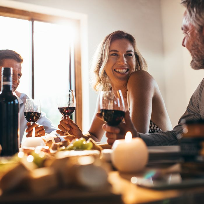 Smiling woman talking with friends sitting at dining tablet at home