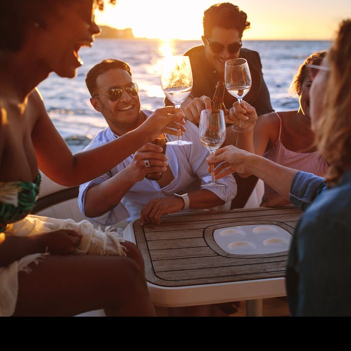Friends cheering over wine at sunset