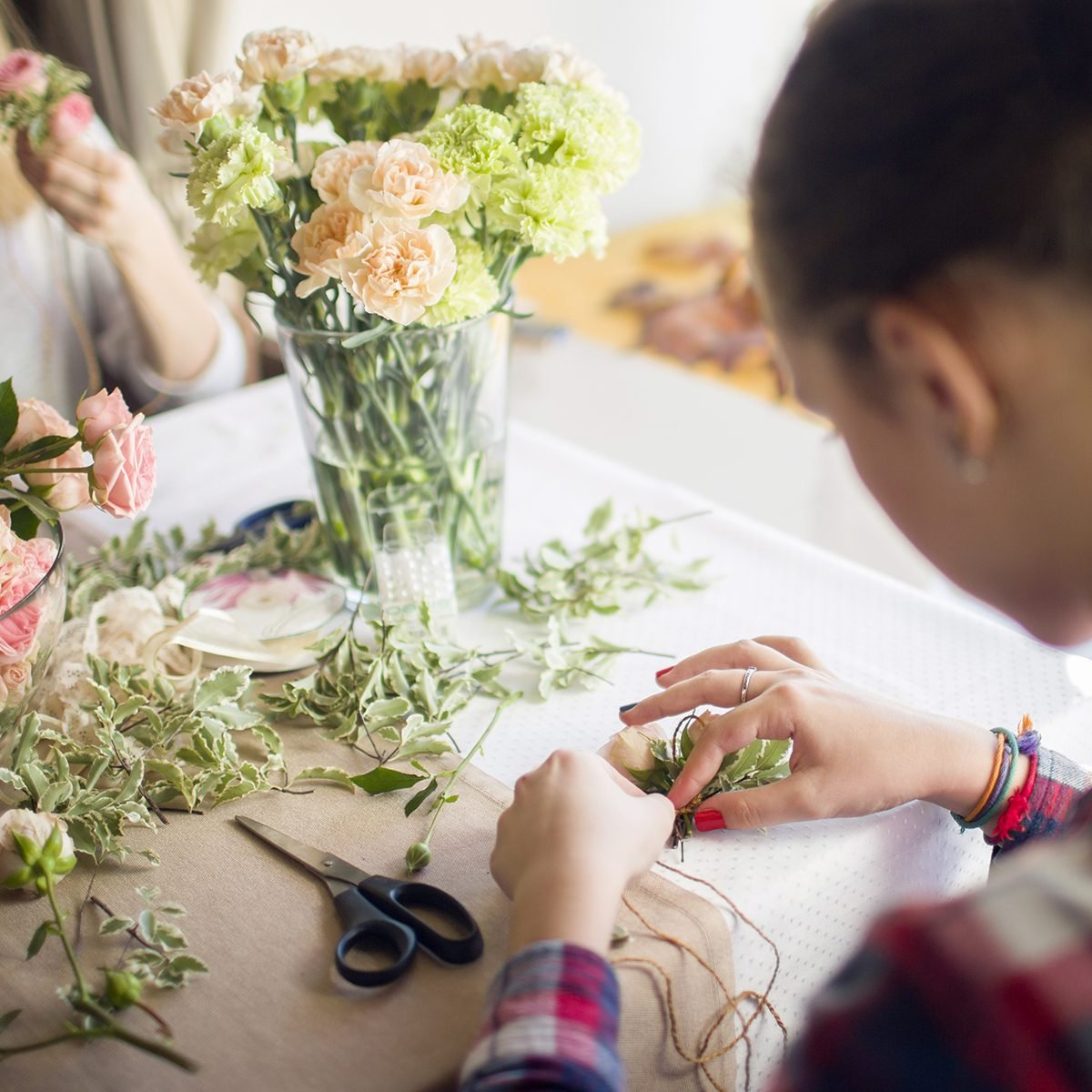 girl mastering a boutonniere on flower masterclass