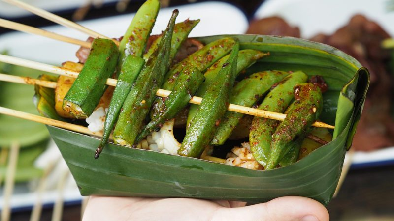 Close up Okra Vegetables and meats are grilled and pour with Hua Jiao Sichuan pepper in banana leaf bowl