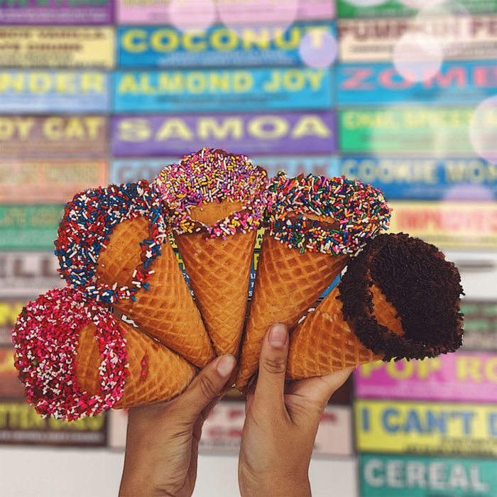Ice cream cones in front of a list of flavors