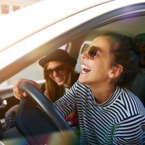Laughing young woman wearing sunglasses driving a car with her girl friend