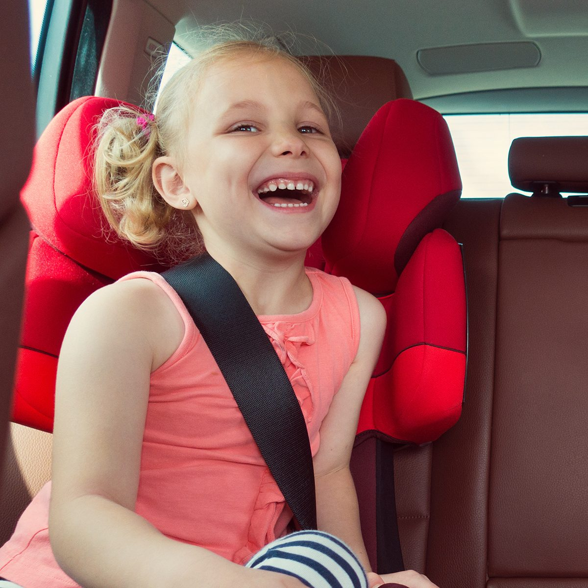 Adorable kid laughing in their car seat