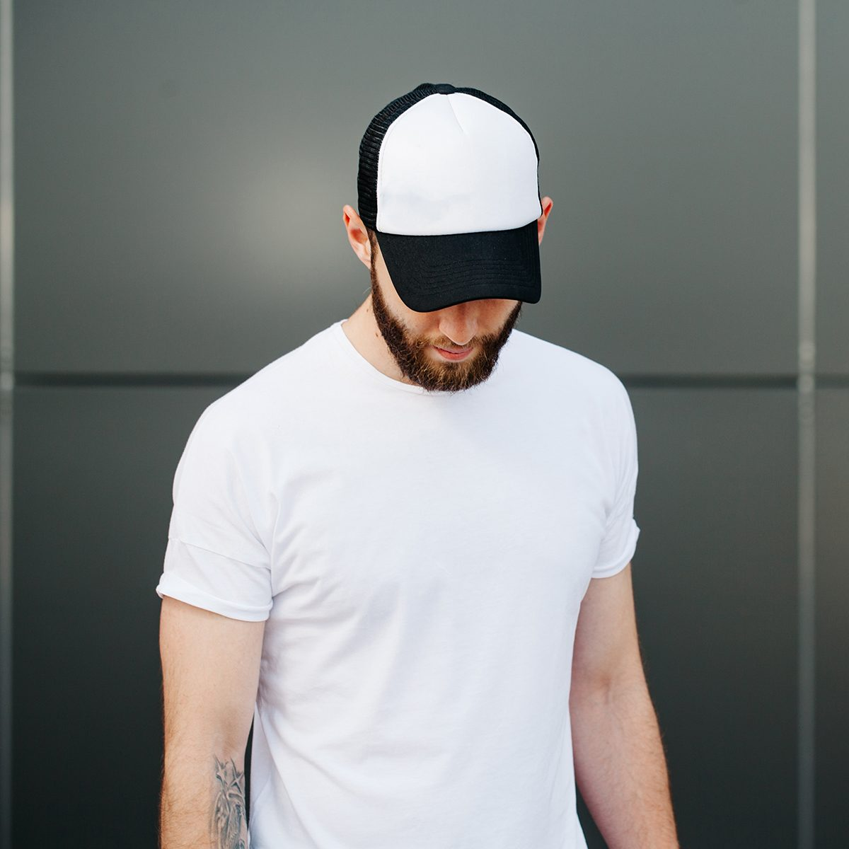 Hipster wearing white blank t-shirt and a cap