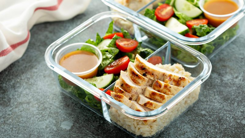 Meal prep lunch box containers with grilled chicken and fresh vegetables