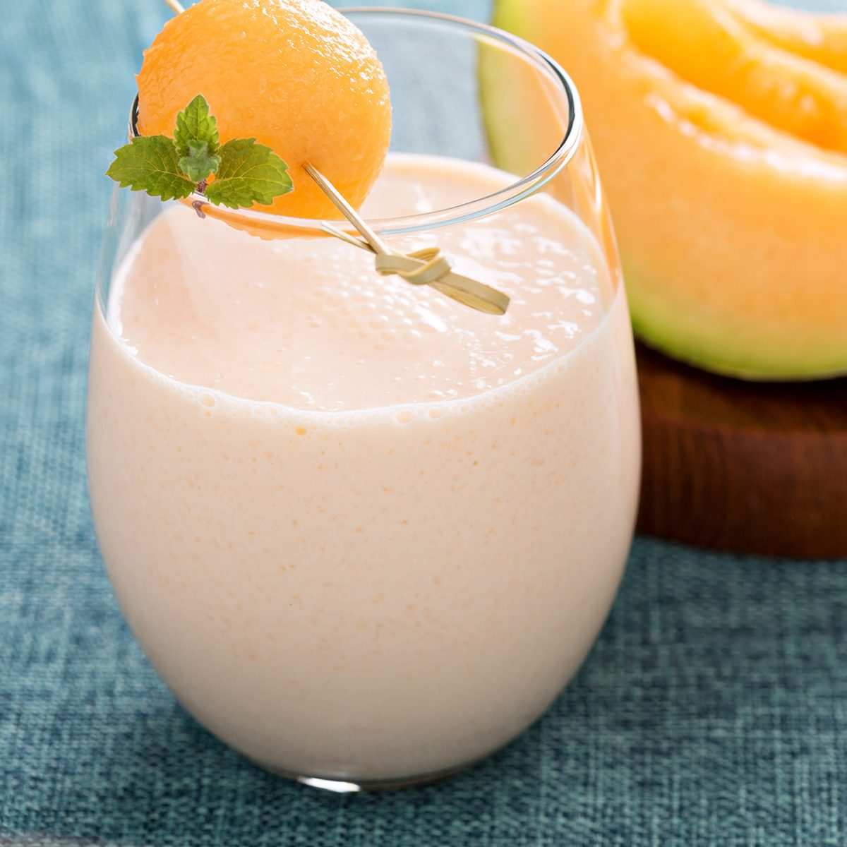 Melon smoothie on a table with light blue linen
