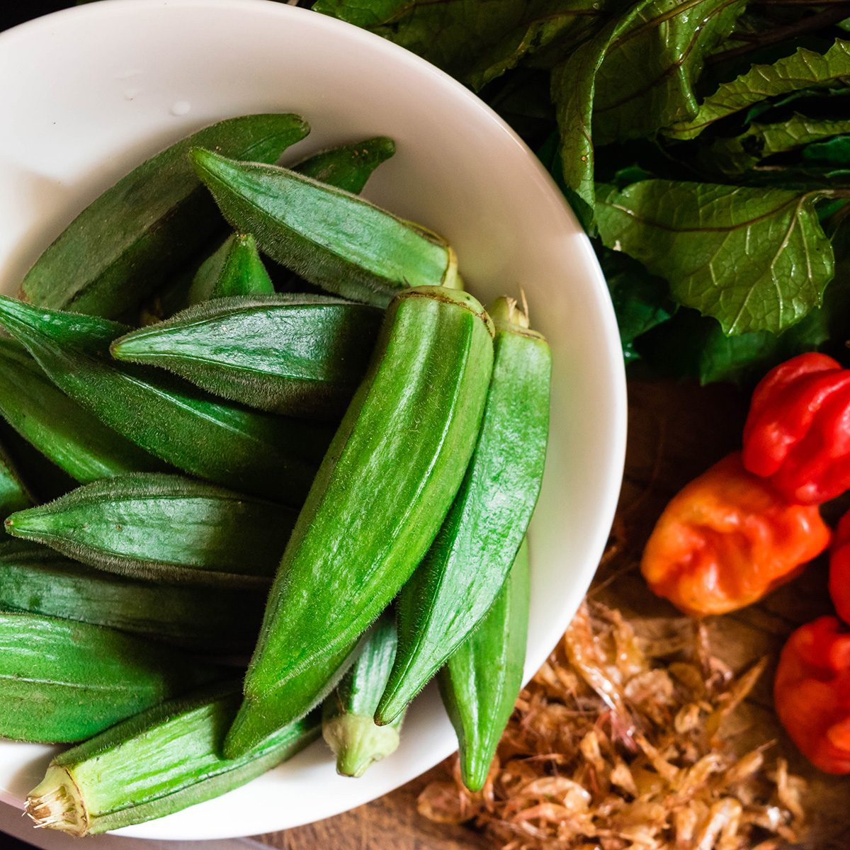 Top view of Farm fresh Raw Green Organic Okra or Lady Fingers in white bowl with red peppers, crayfish and pumpkin leaves or Nigerian ugwu leaves