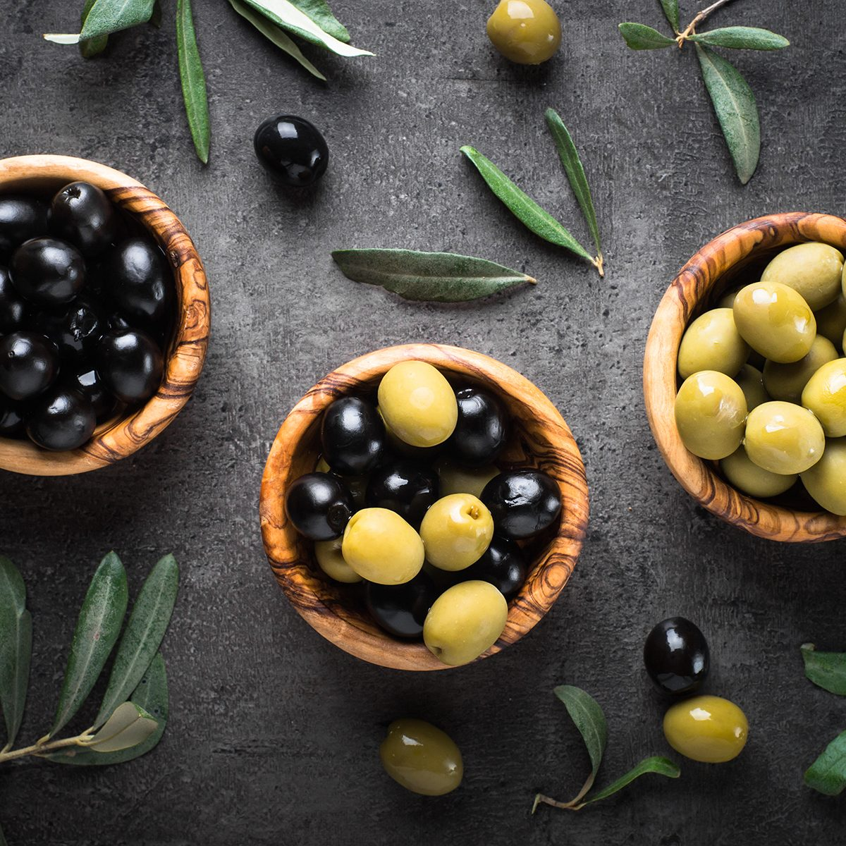 Black and green olives in wooden bowls.
