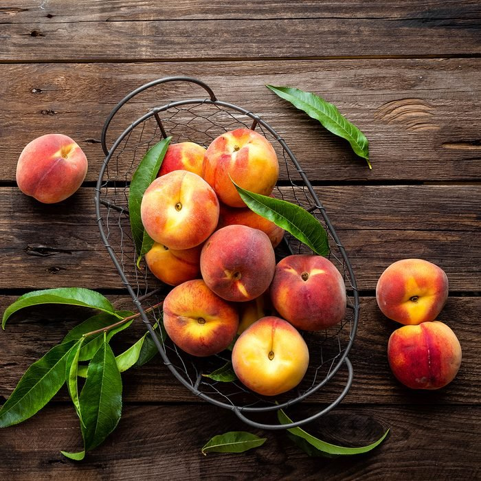 Fresh peaches fruits with leaves in basket on dark wooden rustic background