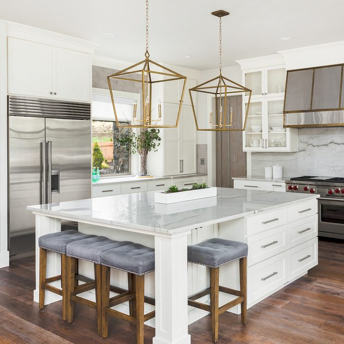 Beautiful white kitchen in new luxury home. Features large island,pendant lights, and hardwood floors