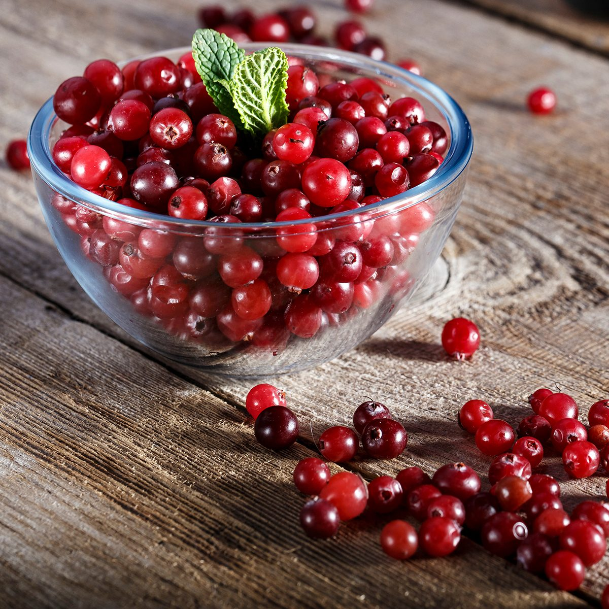 raw fresh cranberries in a plate on a wooden table.