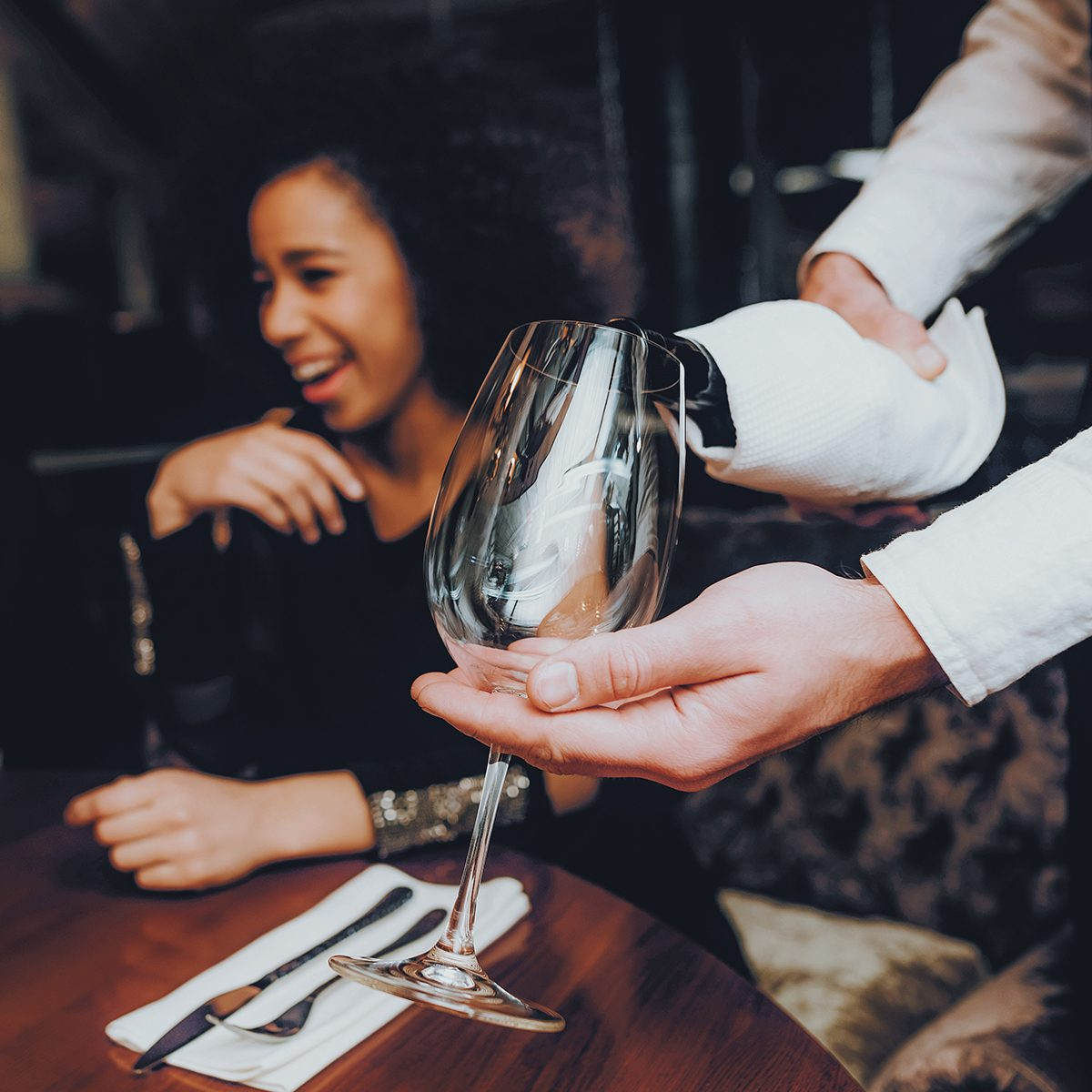Waiter Pouring Wine to Glass Couple in Restaurant.