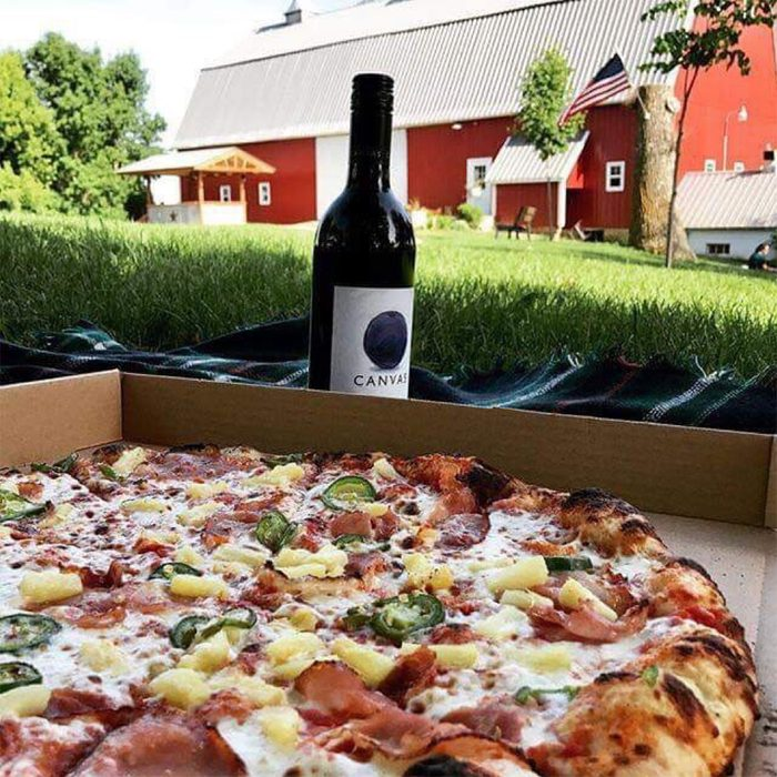 Red Barn Farm pizza and wine bottle on grass with a red barn in the background