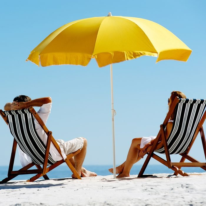 Beach summer couple on island vacation holiday relax in the sun on their deck chairs under a yellow umbrella.