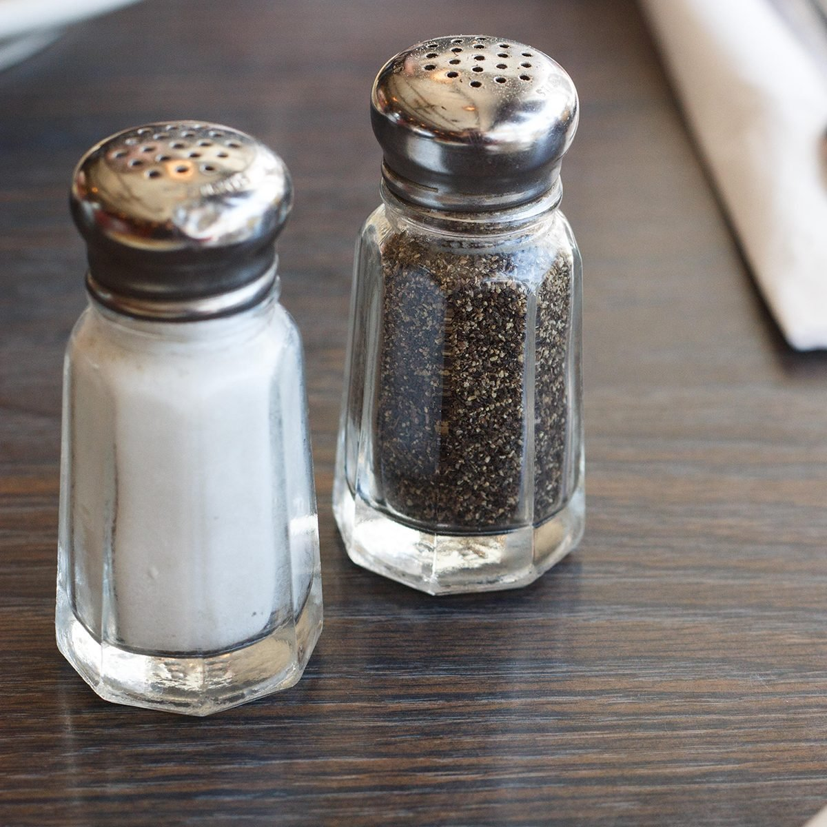 Breakfast scene at a diner with salt and pepper shakers, silverware, and coffee