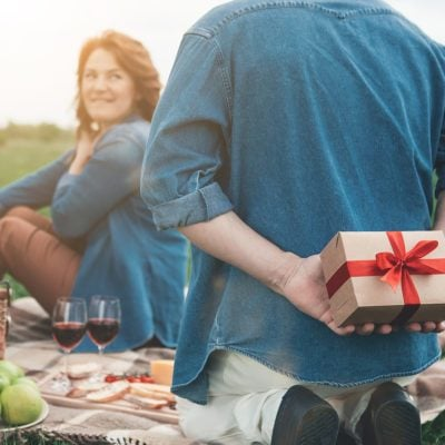 Focus on male arms holding a gift box behind his head. Excited woman is looking at husband with anticipation and smiling. Couple is celebrating anniversary on the grassland ; Shutterstock ID 1101657014; Job (TFH, TOH, RD, BNB, CWM, CM): TOH