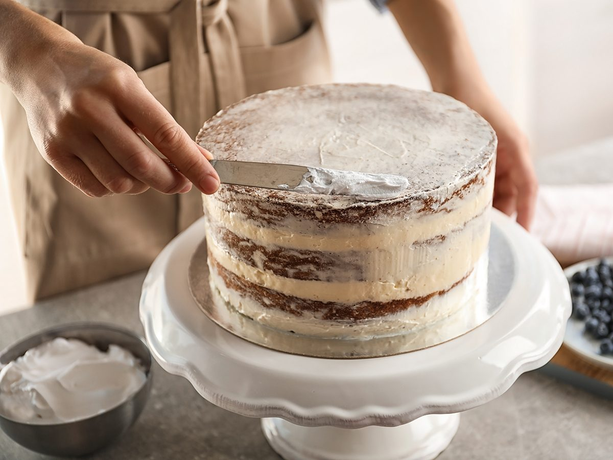 Woman decorating delicious cake with fresh cream on stand. Homemade pastry; Shutterstock ID 1186486588; Job (TFH, TOH, RD, BNB, CWM, CM): TOH