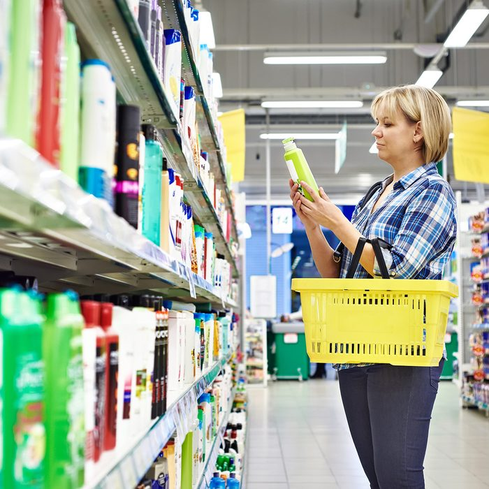 Woman chooses shampoo in cosmetics department in supermarket; Shutterstock ID 251840158