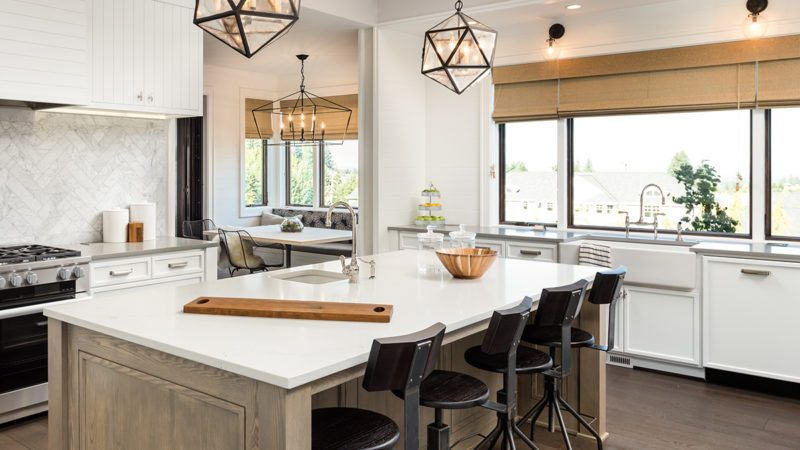 Kitchen Interior with Island, Sink, Cabinets, and Hardwood Floors in New Luxury Home. Features Elegant Pendant Light Fixtures, and Farmhouse Sink next to Window; Shutterstock ID 639915670