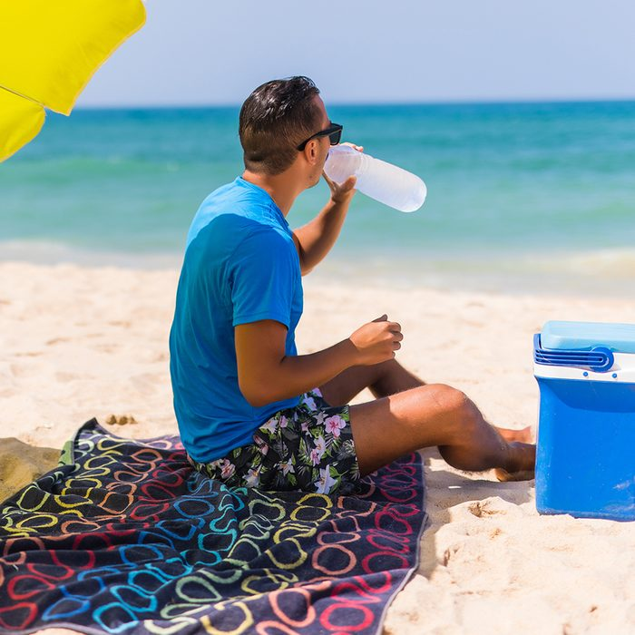 Young man under green solar umbrella drink water from cooler on beach; Shutterstock ID 668276848; Job (TFH, TOH, RD, BNB, CWM, CM): TOH