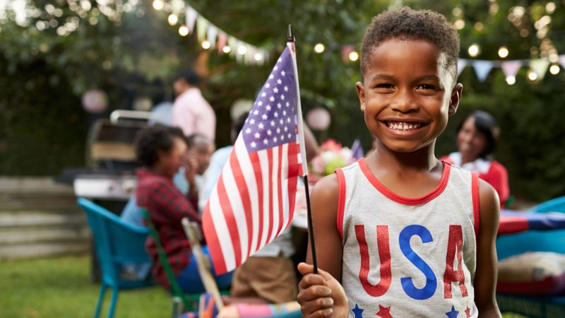 Young black boy holding flag at 4th July family garden party