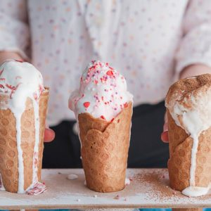 Three ice cream cones on a wooden background
