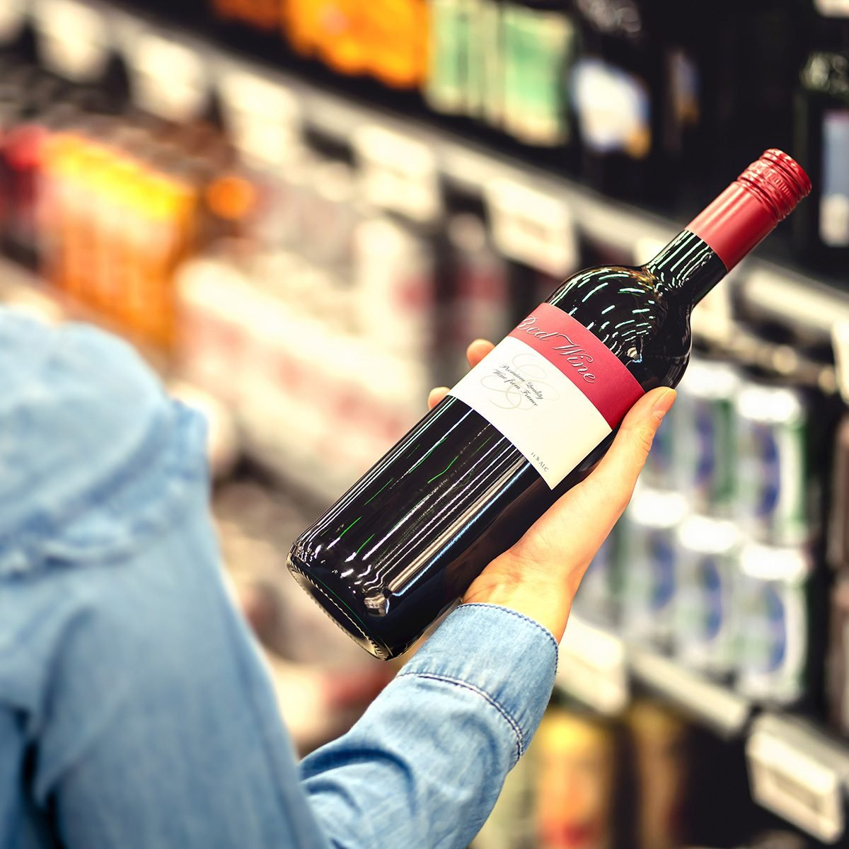 Woman reading the label of red wine bottle in liquor store or alcohol section of supermarket.