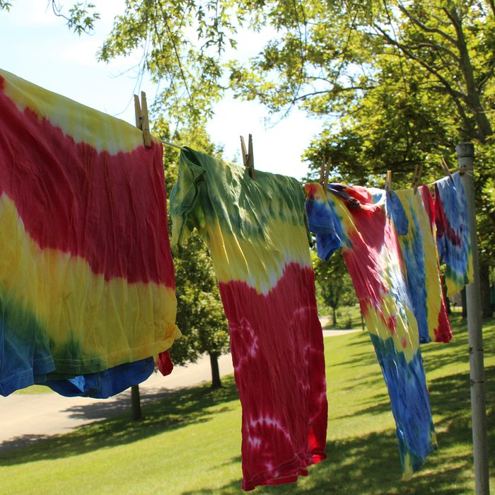 Multi colored tie dye tee shirts hanging on clothesline with trees