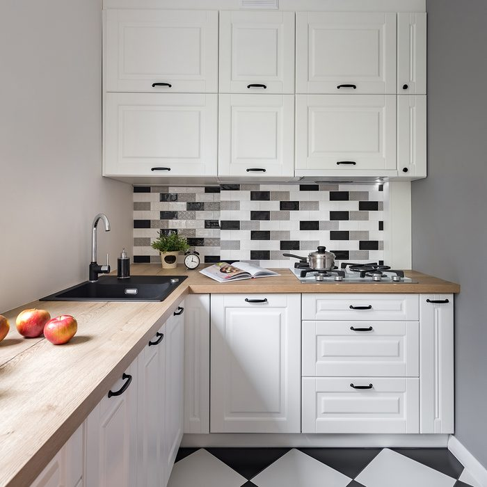 Small kitchen with classic white furniture and modern tiles