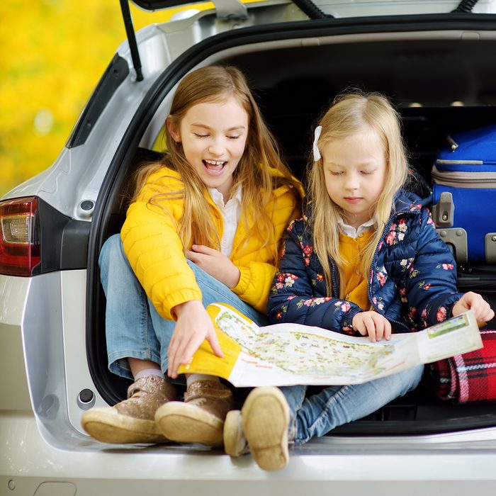 Two adorable girls sitting in a car trunk before going on vacations with their parents.