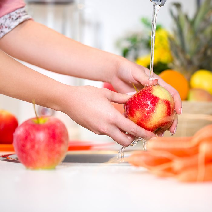 Woman hands washing tasty apple under the tap