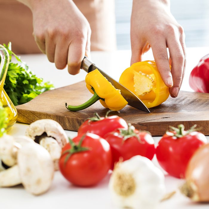 Woman hands cutting vegetables in the kitchen
