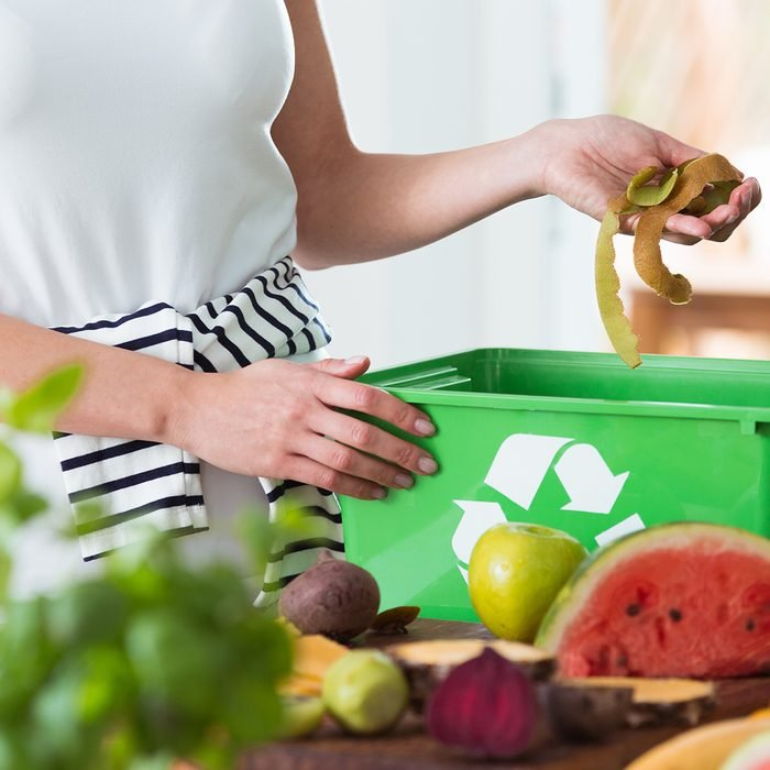 Woman recycling organic kitchen waste by composting in green container during preparation of meal