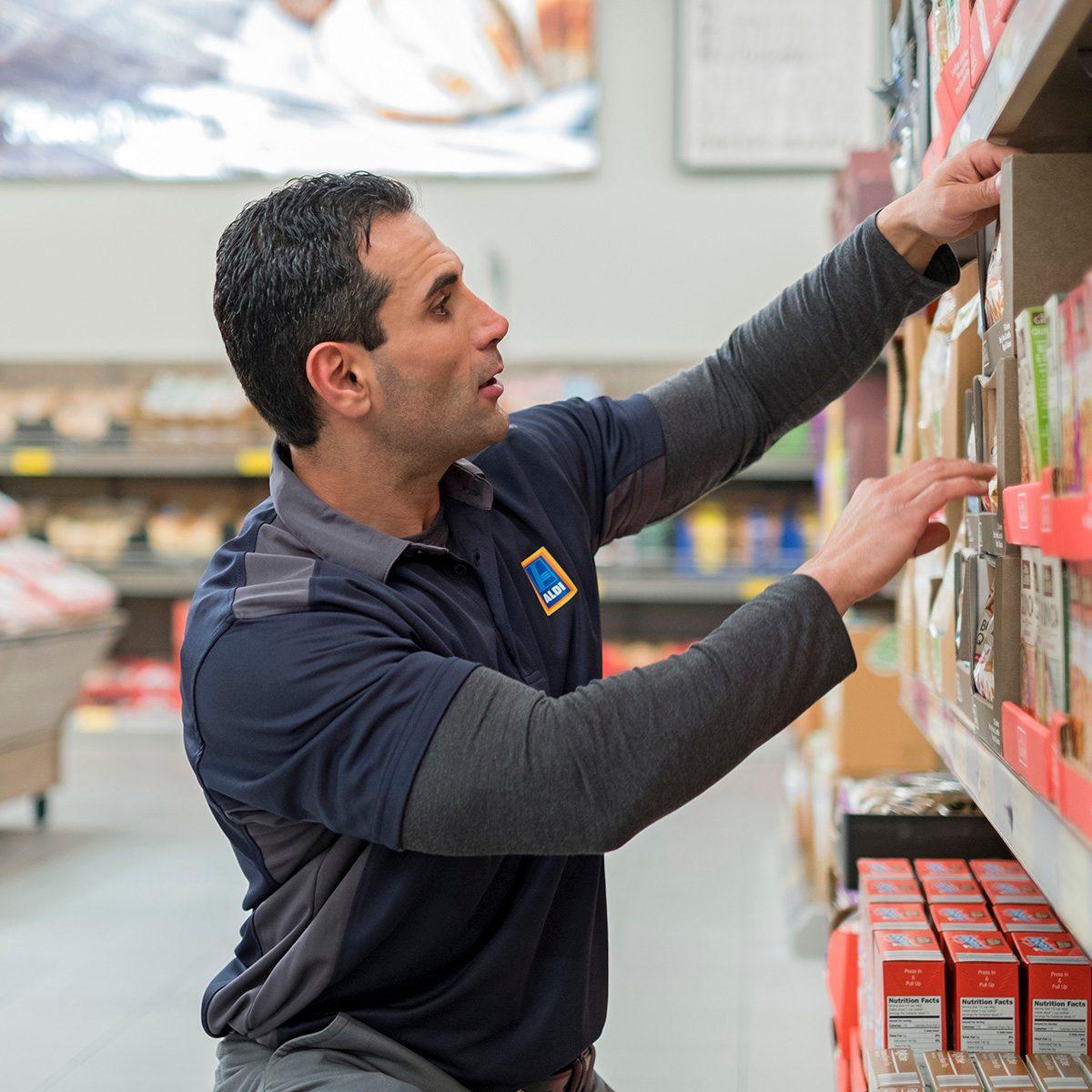 Aldi employee stocking shelf