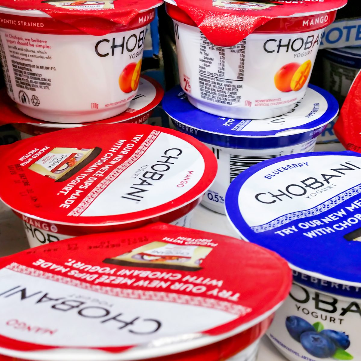 Individual tubs of Chobani brand yogurt on display in a refrigerator for sale in a local supermarket.