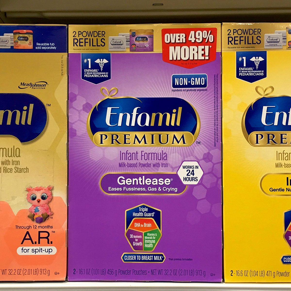 Grocery store shelf with boxes of Enfamil brand baby formula.