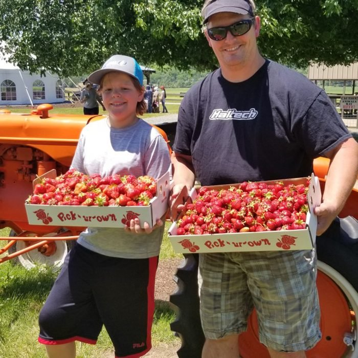 Adult and child holding trays of strawberries